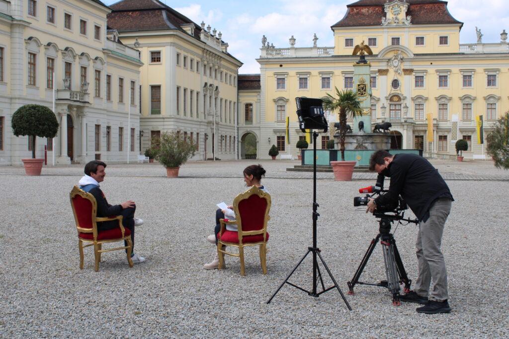 Drei Personen vor dem Residenzschloss Ludwigsburg. Zwei Personen im Interview werden von Kameramann gefilmt.