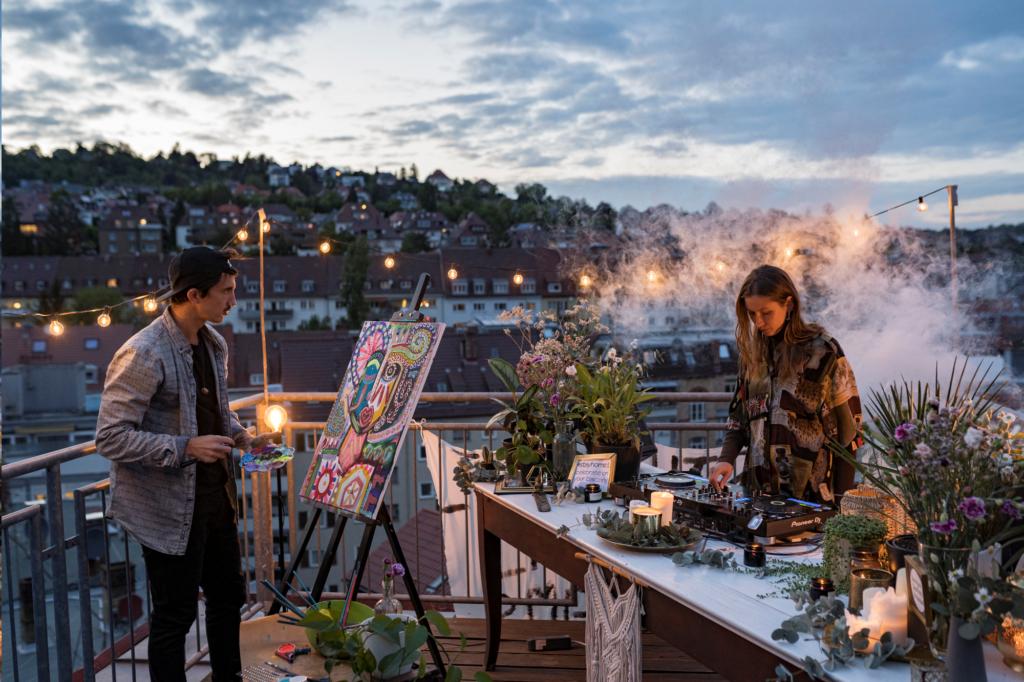 Künstler und Musikerin auf einer Dachterasse in Stuttgart. Sonnenuntergang und Lichterkette sind zu sehen.
